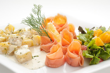 Sliced smoked salmon fillet with boiled potatoes on white plate