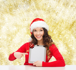 smiling woman in santa hat with gift and tablet pc