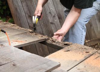 Man takes apart old fence