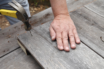 Man recycling old fence wood