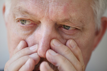 Senior man presses on nostrils