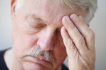 Senior man with painful headache