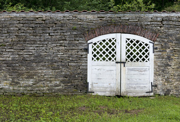 Wall from limestone with gate and a grass before them