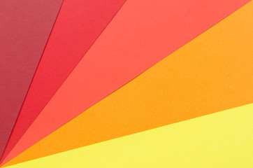 warm-colored construction paper sheets arranged diagonally