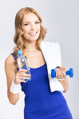 Young woman with water, dumbbell and towel