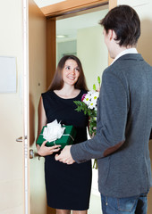Man receives a gift from a woman and flowers