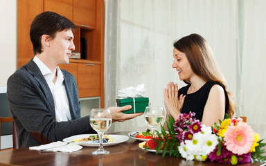 Man giving present to young woman during romantic dinner