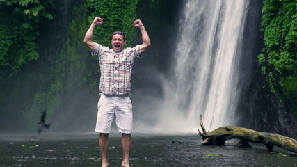 Happy man feeling free next to the waterfall, slow motion 240fps
