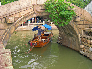 ZHOUZHUANG, SHANGHAI: boat for tourists under an old bridge.