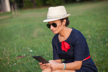 beautiful woman reading e-book in the park