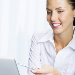 Happy smiling businesswoman working with laptop