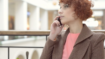 Beautiful  red-haired woman dials and talking on a smartphone