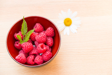Red ripe raspberries in a bowl