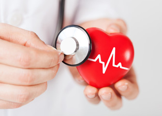 doctor hands holding red heart and stethoscope