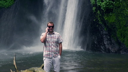 Man talking on cellphone next to waterfall, slow motion 240fps