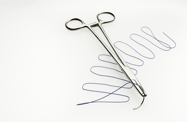Needle holder with a surgical stich
