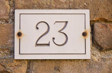 Brass Door Number 23 Mounted on Stone Facade
