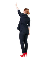 Back view of young redhead business woman pointing at wal