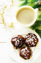 profiteroles with chocolate icing and colored powder and coffee