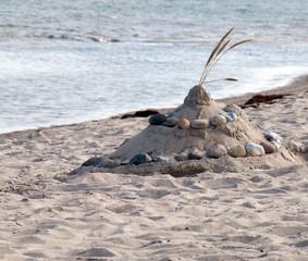 Sandburg mit Steinen