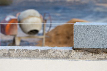 Breeze block wall construction with string line and cement mixer
