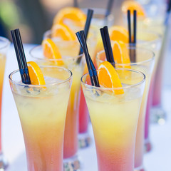 Beautiful line of different coloured cocktails on a open air par