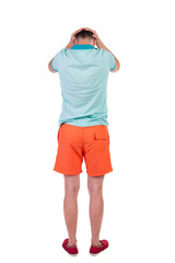 Back view of angry young man in shorts and t-shirt.