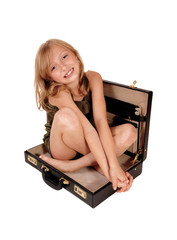 Girl sitting in briefcase.
