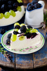 Cheesecake with blackberries and grapes on a wooden table old