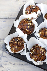 muffins with pumpkin chocolate and oat flakes on baking tray