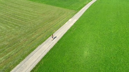 aerial view of woman jogging on country road