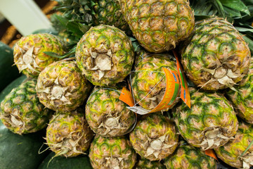 Lots of pineapples on supermarket stall