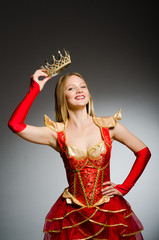 Queen in red costume against dark background