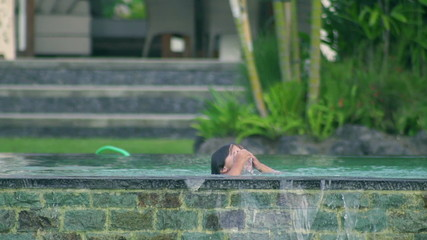 Boy coming put from water in the pool, slow motion shot