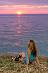 Girl on sea sitting and looking at the sunset