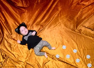 baby lies in a leopard suit