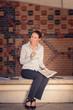 canvas print picture - Attraktive junge Frau sitzt auf einer Bank und lacht