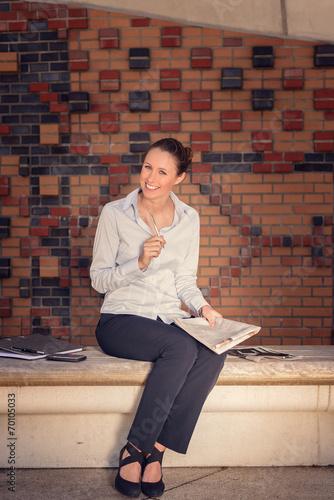 canvas print picture Attraktive junge Frau sitzt auf einer Bank und lacht