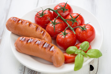 Grilled sausages with roasted tomatoes and green basil, close-up