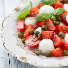 Close-up of caprese salad with capers and fresh mint, close-up