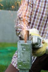 Handwerker sägt mit Flex Metall zu, Funken