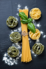 Raw spaghetti and tagliatelle with fresh green basil, above view