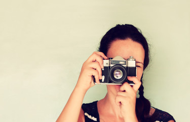 young woman holding old camera. vintage effect