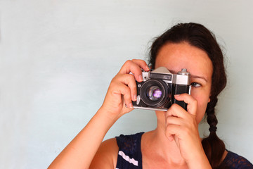 young woman holding old camera
