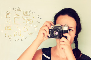 young woman holding old camera and varius sketches as h