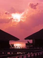 Human silhouette in water bungalow at sunset