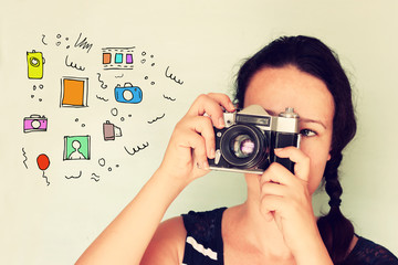 young woman holding old camera and varius colorful sketches as h
