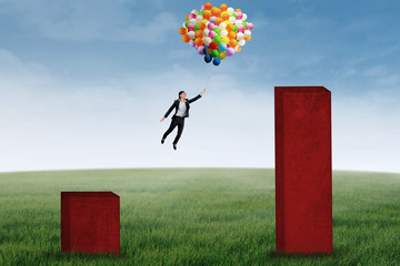 Businesswoman flying with balloons to higher graph 1