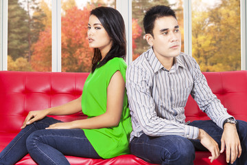 Couple quarreling and sitting separately