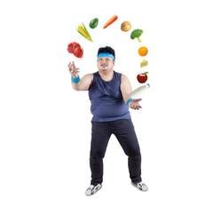 Fat man juggling healthy food